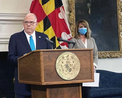 Maryland Commerce Secretary Kelly Schulz listens as Maryland Gov. Larry Hogan eases several coronavirus restrictions in the state. (Bryn Stole/Baltimore Sun).