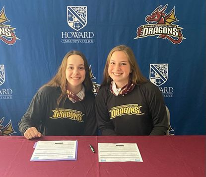 Sarah Phelps, left, and Samantha Hobert pose for a photo together after signing to play softball at Howard Community College next spring.