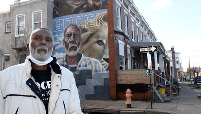 Rocky Brown stands at the corner of E. Madison and Curley Streets, where a mural was painted in his honor (visible in background.) He is the president of his local community association (Bocek/Madison East End Community Association) and has lived in his home for 11 years. In December, he and his wife were facing eviction. December 22, 2020