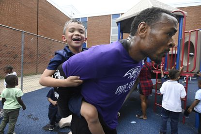 Ravens cornerback Brandon Carr gives Pre-K student Alec Wilson, 5, a piggyback ride around the playground at Calloway Elementary School. The Ravens host a volunteer day to help transform and refurbish the Webster Kendrick Boys & Girls Club's multi-purpose room at Calloway Elementary School. Current and former players, staff join representatives of M & T Bank for the project.