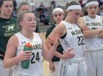 McDaniel's Josey Klingenberg (L) and sister, Jayce are front and center in a team huddle during the Green Terror's 66-57 loss to Gettysburg Wednesday night in Westminster.