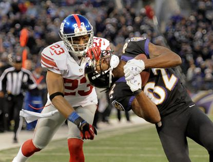 Ravens wide receiver Torrey Smith, right, makes a catch in front of Giants cornerback Corey Webster in the first quarter.