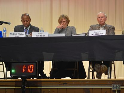 Baltimore County Planning Board Chairman Scott Phillips and members Cathy Wolfson and Wayne McGinnis listen to testimony during a public hearing at Lansdowne High School March 3.