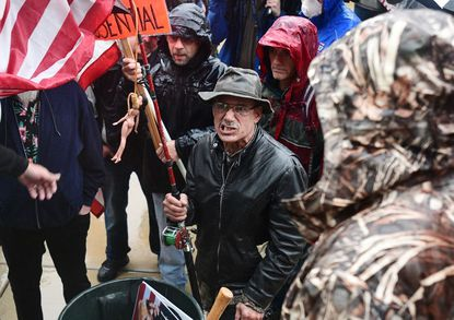 A man with a flag that had a doll with a noose around its neck attached to it came to the front of the stage during a protest against the state's stay-at-home order at the Michigan Capitol in Lansing on Thursday, May 14, 2020.