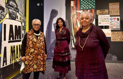 "Wanda Draper, interim executive director of the Reginald F. Lewis Museum of Maryland African American History & Culture, center, with guest curators, Dr. Leslie King Hammond, left, and Dr. Lowery Sims, right, at the new exhibition, ""Make Good Trouble: Marching for Change."" The exhibition explores racial justice protests in Maryland last summer, with paintings, protest signs and video."