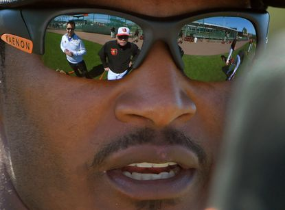 Orioles outfielder Adam Jones talks to executive vice president Dan Duquette (wearing white) and manager Buck Showalter, who are both reflected in the center fielder's shades during spring training at the Ed Smith Stadium complex on Feb. 26, 2016.