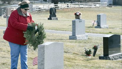 Jennie Lou Goff honors a Veteran during the Wreaths Across America Day program at Deer Park Methodist Cemetery in Smallwood on Satrurday December 16, 2017.