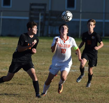 Fallston's Christo Hondrogiannis and Rising Sun's Zachary Seigel sprint to the loose ball during Wednesday afternoon's playoff match at Rising Sun.