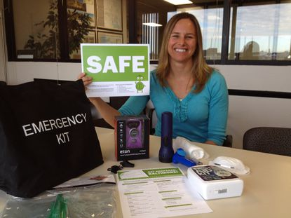 """Baltimore city planner Kristin Baja holds up the """"safe"""" window placard in an emergency kit distributed to residents at community meetings held to encourage disaster planning and preparedness."""