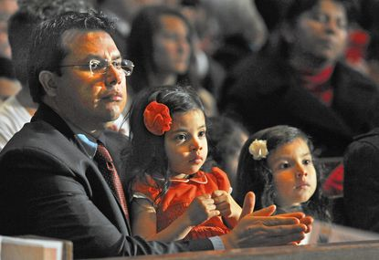 Diego Niño, of Pikesville, with his daughters, Chiaru, left, and Liliana Niño, at the Mass of Thanksgiving to celebrate the 225th Anniversary of the Archdiocese of Baltimore at the Cathedral of Mary Our Queen.