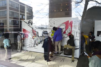 A group of students from ConneXions Community-Based Art School work on a mural.