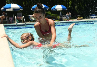 Lifeguard Chloe Lehane gives individual instruction to 8-year-old Charlie Knight during a swim lesson at Rollingwood Pool in Catonsville on Wednesday, June 23, 2021.