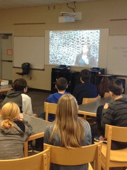 Students at Mt. Airy Middle School watch as Izzie Fuqua, on screen, is about to demonstrate how chainmail armor holds up against a medieval sword.