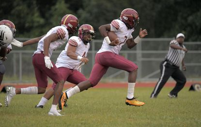 New Town cornerback Darron Broach (left) and defensive tackle Walter Ransom II chase Gerrell Johnson (7), who picks up an Owings Mills fumble for a touchdown during the first Ravens Rise game of the 2019 season.