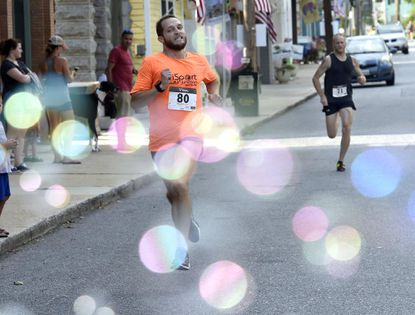 Chris Mead runs through bubbles at the finish line to win the Coolest Mile on Main Street race in downtown Sykesville Saturday August 12, 2017.