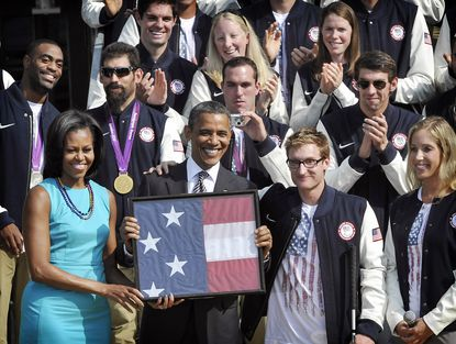 Navy Lt. Brad Snyder, third from left, who has won seven gold medals at the Warrior Games in Colorado Springs, Colo., as well as one silver and two gold medals at the Paralympic Games in London, helped present President Barack the flag from London.
