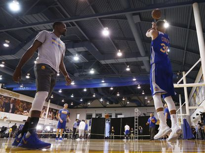 Golden State Warriors player Kevin Durant walks past while teammate Stephen Curry takes a shot during practice at the Warriors practice court in Oakland on June 3, 2017.