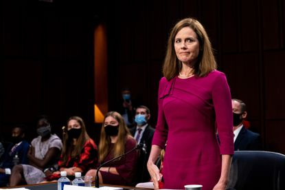 Judge Amy Coney Barrett, with her family behind her, is sworn in to testify before the Senate Judiciary Committee on the first day of her Senate confirmation hearing in Washington.