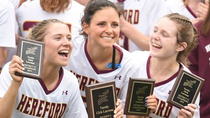 Hereford players, from left, Stephanie Joyce, Libby May and Bella Cavallaro show off their plaques as they celebrate their win over Catonsville during the Baltimore County girls lacrosse championship at the US Lacrosse field in Sparks on Saturday, May 4.