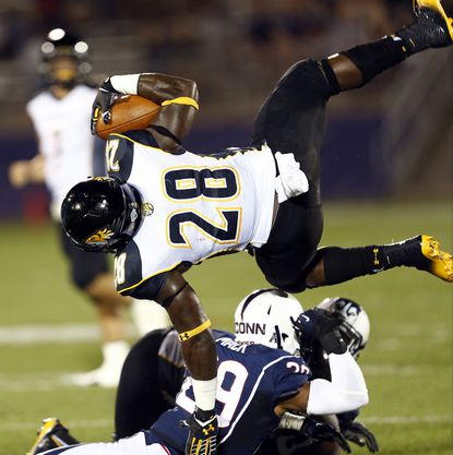 Towson running back Terrance West is tackled by Huskies cornerback Taylor Mack.