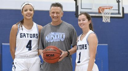 Mike Buchanan, center, an assistant coach for the Notre Dame of Maryland University women's basketball team and a 1971 graduate of Towson High, stands with NDMU freshmen Daija Fitchett, left, and Maci Lopez, who are both 2018 graduates of Towson High.