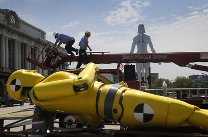"""A worker on Thursday gets ready to erect a giant car crash dummy sculptor sponsored by the Highway Association for the """"Roadside Attractions"""" exhibit for this year's Artscape."""