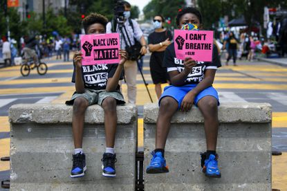 """Tyshawn, 9, left, and his brother Tyler, 11, right, of Baltimore, hold signs saying """"Black Lives Matter"""" and """"I Can't Breathe"""" as they sit on a concrete barrier near a police line as demonstrators protest along a section of 16th Street that has been renamed Black Lives Matter Plaza, Wednesday, June 24, 2020, in Washington. George Floyd's plea of """"I can't breathe,"""" to the officer kneeling on his neck, holds the number two position on the Yale Law School librarian's list of the most notable quotes of 2020. (AP Photo/Jacquelyn Martin)"""