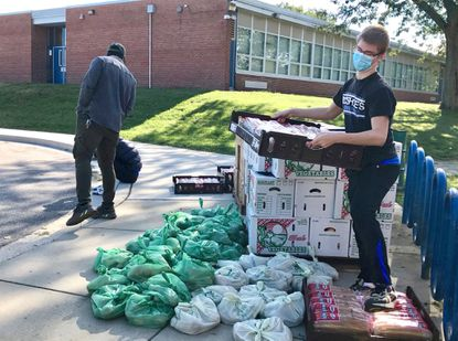Parkville High School student Ryan McCann, 14, carries a pallet of bread at the Hillendale Police Athletic League building in Parkville on Sept. 19. He is one of the students hired by the county to help provide free meals each week from now until late December, when their work contracts end.