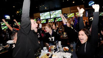 Stephen Davis, left, Julia Woods, right, and other patrons celebrate at Buffalo Wild Wings in Westminster during the Baltimore Ravens' AFC Championship win over the New England Patriots in 2013. BWW and other Carroll establishments expect good Super Bowl crowds on Sunday.