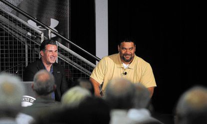 Under Armour CEO Kevin Plank, left, talks to Haloti Ngata of the Baltimore Ravens at the shareholders meeting.