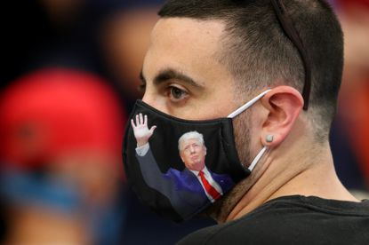 A man wears a face mask featuring Donald Trump before the Fighters Against Socialism event at American Top Team in Coconut Creek, Florida Sunday.