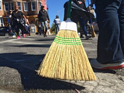 A resident sweeps while other volunteers cross North Avenue to help clean up after the 2015 rioting that broke out on the day of Freddie Gray's funeral in West Baltimore.