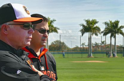 Orioles manager Buck Showalter,left and executive vice president Dan Duquette chat while they watch pitchers throw during spring training at the Orioles' spring facility Saturday, Feb. 21, 2015, in Sarasota, Fla.