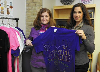 Stephanie Goldenberg, left, and Mary Bachkosky, right, hold T-shirts that were designed by students as part of the Anne Arundel Community College Clothesline Project which raises awareness of domestic violence.