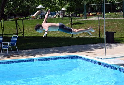 Ezra Agboli, 13, dives off the diving board at Stevens Forest Pool on Memorial Day 2021. This is the first weekend of Columbia Association pools have opened since 2019.