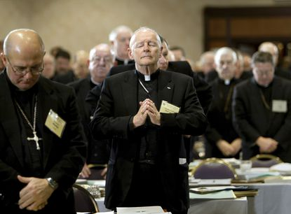 FILE - In this Nov. 10, 2003 file photo, Cardinal Theodore Edgar McCarrick, Archbishop of Washington, D.C., center, joins fellow clergy in prayer at the end of the opening session of the U.S. Conference of Catholic Bishops meeting in Washington. McCarrick – who was defrocked by Pope Francis in 2019 – served as head of Catholic dioceses in Metuchen and Newark, New Jersey, and in Washington. A report released by the Vatican on Monday, Nov. 9, 2020, found that three decades of bishops, cardinals and popes dismissed or downplayed reports of McCarrick's misconduct with young men. (AP Photo/J. Scott Applewhite, File)