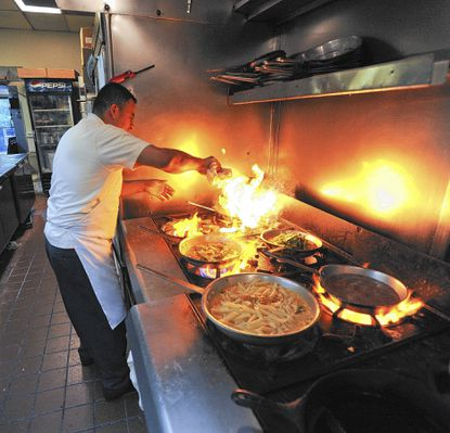 Santos Vasquez puts a little fire into his Italian dish being prepared in the kitchen of Liberatore's Ristorante. The restaurant in Eldersburg was part of the original group that offered special deals for Restaurant Week four years ago and is one of 24 in the county participating in the annual event this week.