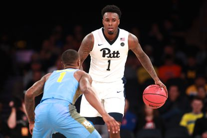 JamelArtis of the Pittsburgh Panthers drives past Duane Wilson of the Marquette Golden Eagles in the second half of the 2K Classic at Madison Square Garden on November 18, 2016 in New York.