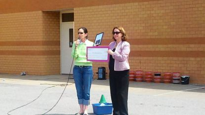 Mount View Middle School principal Kathryn McKinley, left, presents a check to Maryland Zoo representative Anne Finney during the school's Green Field Day.
