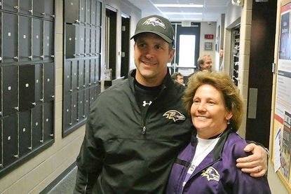 Charlotte Krause, president of the Council of Ravens Roosts, with Ravens coach John Harbaugh.