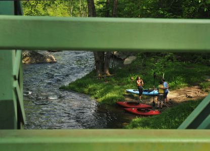 Kayakers on the Gunpowder seen through the Falls Road bridge. Frequent flooding of the Gunpowder River is causing erosion, harming the river and its native trout populations, and may threaten the safety of anglers, according to Gunpowder Riverkeeper Theaux Le Gardeur.