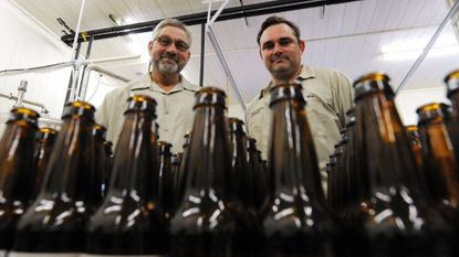 Henry Ruhlman, left, and his son Matt pose for a photo behind bottles of the Our Ales brewery's Milk Stout beer on the Hampstead farm where they grow their hops, brew the beer and host a disc golf course. Photo taken Tuesday, June 17, 2014.