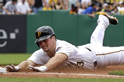 Travis Snider dives safely into third base with a triple during a game against the Cubs.