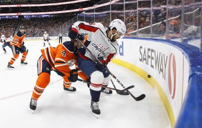 Washington Capitals' Chandler Stephenson (18) and Edmonton Oilers' Kris Russell (4) vie for the puckduring the first period of an NHL hockey game Thursday, Oct. 24, 2019, in Edmonton, Alberta. (Jason Franson/The Canadian Press via AP)