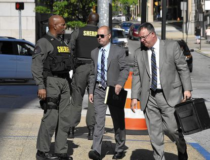Lt. Brian Rice (center) arrives at the courthouse with his lawyer Mike Davey, right, for the second day of his trial.