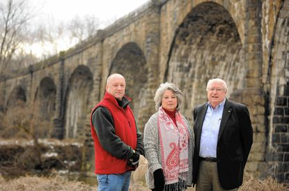 Members of the board of Patapsco Heritage Greenway include, from left, Oella resident Steve Stannard, Catonsville resident Victoria Goodman and president John Slater, of Columbia, are shown at the Thomas Viaduct near the border between Baltimore and Howard counties.