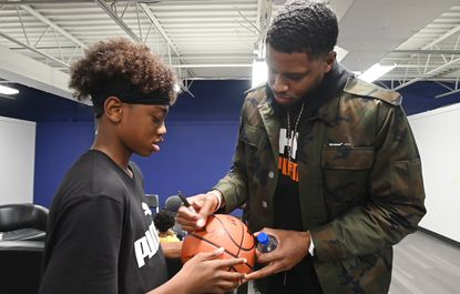 San Antonio Spurs player and Baltimore native Rudy Gay, right, signs a ball for young fan during visit to the PickUp USA Fitness gym in Towson on November 19.
