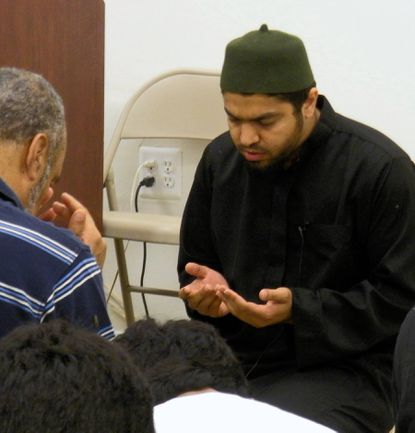 Sheikh Abdullah Helmy recites a prayer along with members of the Masjid Al-Falaah community during a dinner Saturday bringing together Muslims and members of other faiths.