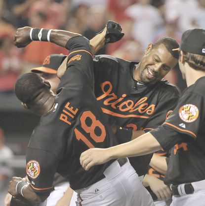Derrek Lee celebrates with Felix Pie and other teammates after he smacked a solo homer off Cincinnati's Jose Arredondo in the 12th inning to give the Orioles a 5-4 win.