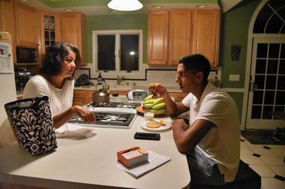 Severna Park, Md. -- Sonal Parikh speaks with her son, Rohan Parikh, 15, as he eats breakfast before school early Tuesday morning. Rohan, a sophomore in the STEM Magnet program at South River High School, often wakes up at 4:45 a.m. on days he rides the bus to school.